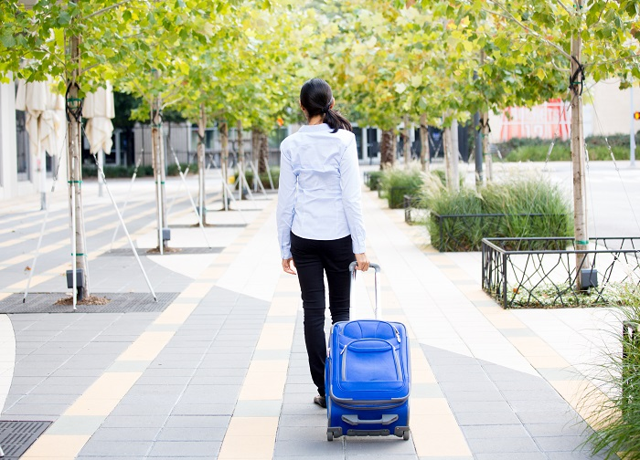 Expat-life-saying-goodbye-Woman-walking-away-with-a-blue-suitcase-.jpg